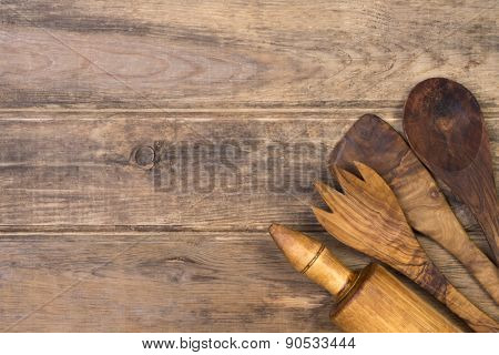 Wooden kitchen utensils on wooden background with copy space
