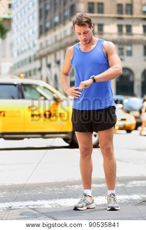 Runner looking at smartwatch heart rate monitor having break while running in New York City, Manhattan. Man jogging outside looking at sports smart watch training for marathon. Male fitness model