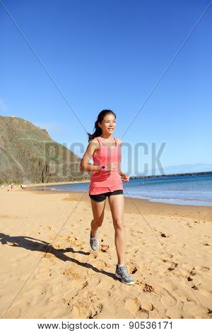 Runner sports athlete running woman on beach sweating and jogging. Fit exercising female fitness model working out training for marathon run. Biracial Asian Caucasian sports girl.
