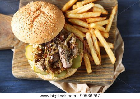 Tasty burger and french fries on wooden table background , close-up Unhealthy food concept