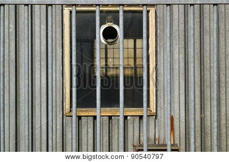 Vista through an industrial barrack window behind a fence