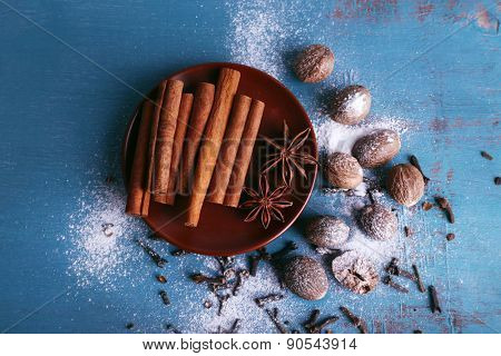 Cinnamon sticks, star anise, nutmeg and cloves on color wooden table background