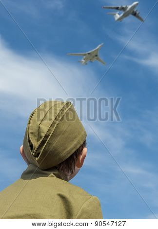 MOSCOW - MAY 9, 2014: Victory day celebrations in Moscow. A little boy in a military garrison cap watches the flight of military aircraft