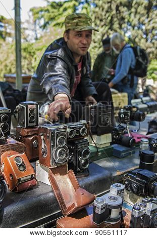 TBILISI, GEORGIA - MAY 01, 2014: An unidentified seller on Dry Bridge market in Tbilisi sells vintage photo equipment, Georgia. Dry bridge today is most famous flea market in Georgia.