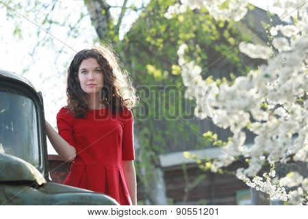 Blue-eyed Brunette Standing On Truck's Running Board At Blooming Fruit Trees Background