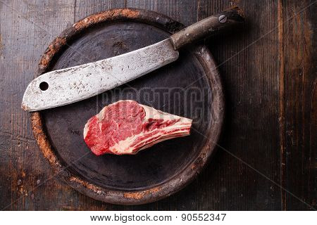 Raw Meat Ribeye Steak Entrecote And Meat Cleaver On Dark Background