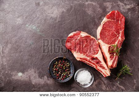 Heart Shape Raw Fresh Meat Ribeye Steak With Rosemary, Pepper And Salt On Stone Slate Background