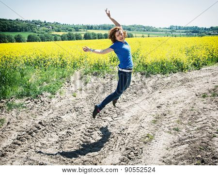Positive Young Woman Is Jumping In Rapeseed Field