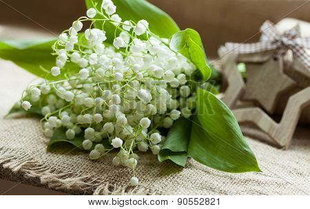 Blooming lilly of the valley on rustic textile background