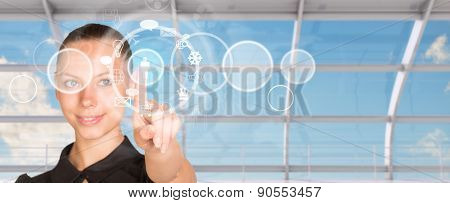 Young businesswoman pressing on holographic screen