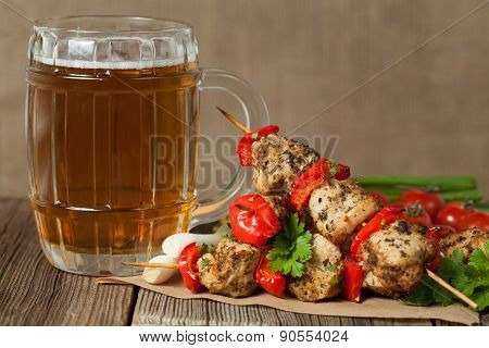Gourmet chiken kebab skewer barbecue meat on bamboo sticks with glass of beer. Rustic table backgrou