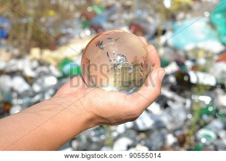 Globe In Hands On Garbage Background.
