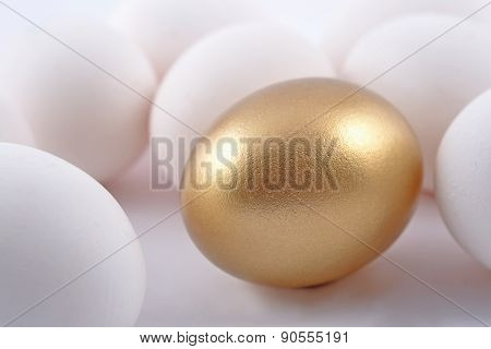 Golden Egg And Jast Eggs On A White