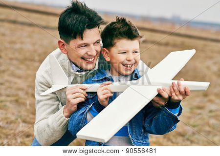 Cheerful boy and his father playing with toy airplane outside