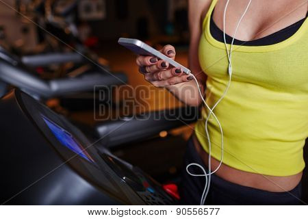 Fit girl with smartphone in sports club