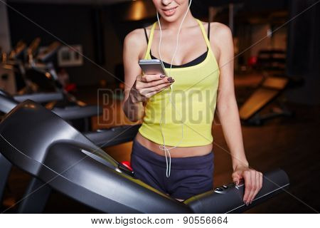 Fit girl with smartphone listening to music in sports club