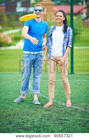 Young couple playing with disc on green lawn