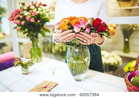 Female florist holding fresh roses in vase