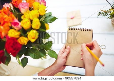 Hands of florist with pencil making notes