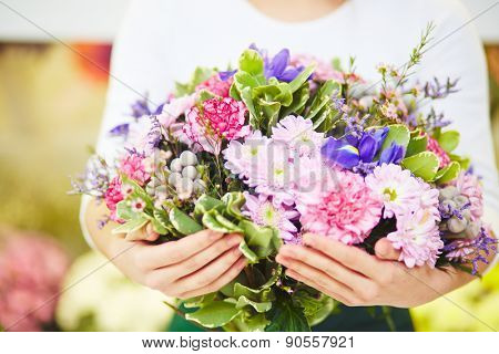 Florist holding big bouquet of fresh flowers