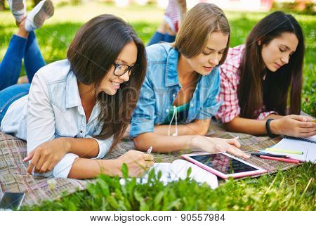 Modern teen girls doing schoolwork outside