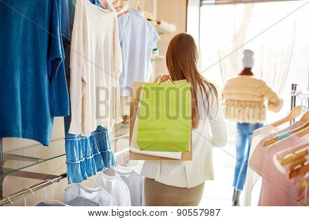 Back view of young woman with paperbags standing in boutique