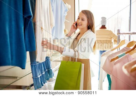 Modern woman speaking on the phone while looking through new collection of clothes in boutique