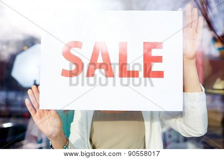Female holding paper with sale announcing?