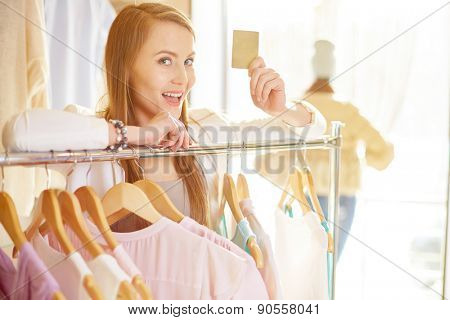 Cute shopper showing discount card in clothing department