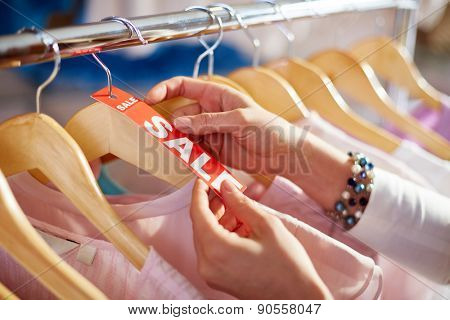 Female hand holding sale label on one of hangers with collection of clothes