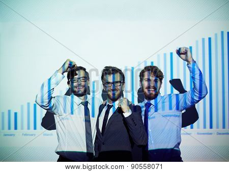 Ecstatic businessmen standing by wall with increase chart on it