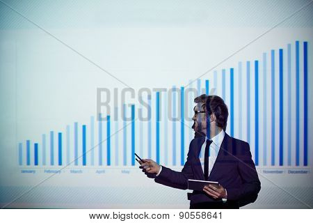 Successful businessman with touchpad presenting data in chart
