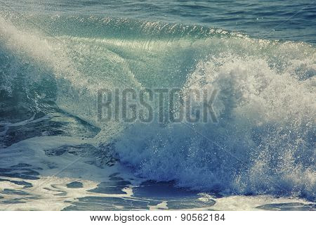 Beautiful ocean wave breaking, abstract background done with a vintage retro instagram filter.