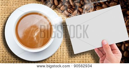 Hand showing card against coffee beans and burlap sack