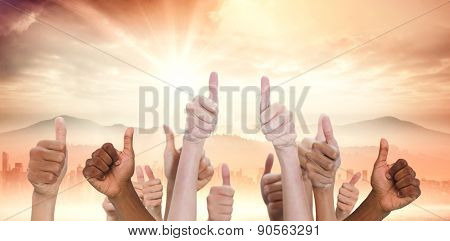 Hands showing thumbs up against sun shining over road and city