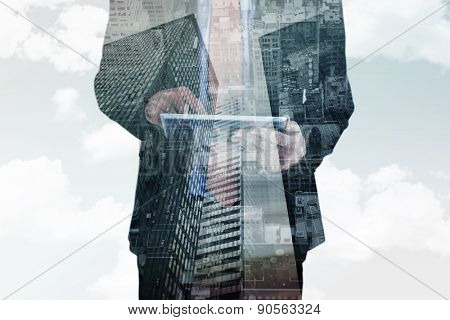 Businessman scrolling on his digital tablet against low angle view of skyscrapers