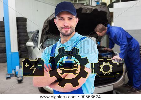 Smiling male handyman in coveralls standing arms crossed against mechanic examining car engine