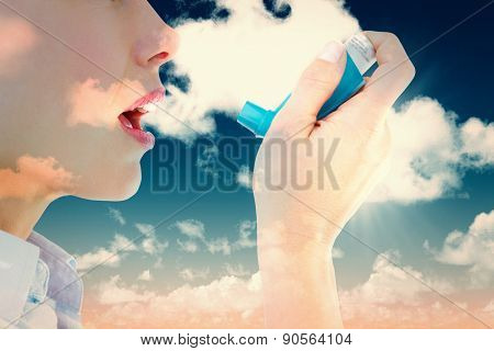 Close up of a woman using an asthma inhaler against blue sky