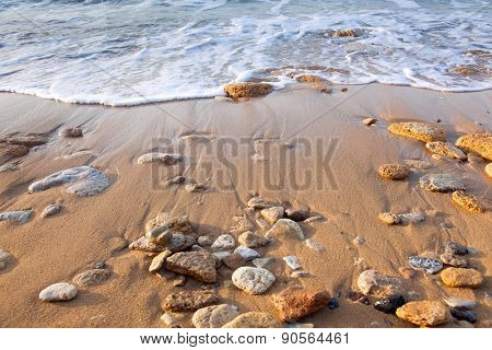 Wave of the sea on the beach  with sand and stones - summer background
