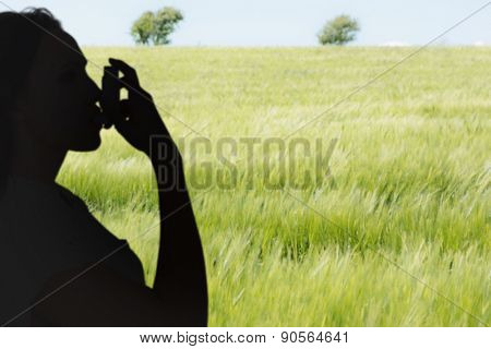 Asthmatic brunette using her inhaler against green meadow