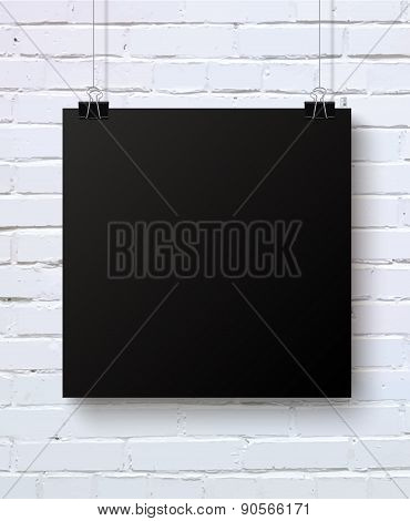 Black blank piece of paper on the white brick wall