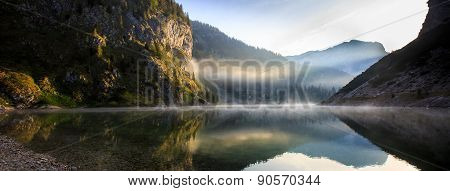 Mountain Lake Scenery With Sun Shining To The Rocky Slope