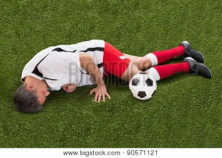 Injured Soccer Player Lying On Grass
