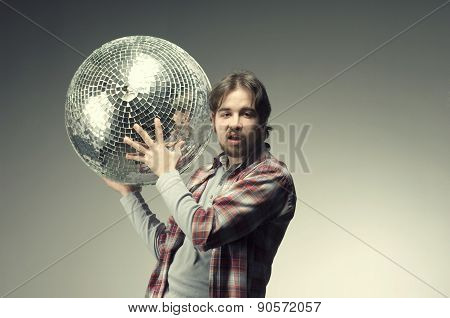 Young man posing with a disco ball