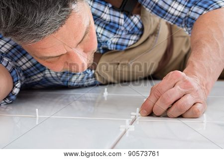 Handyman Placing Spacers Between Tiles