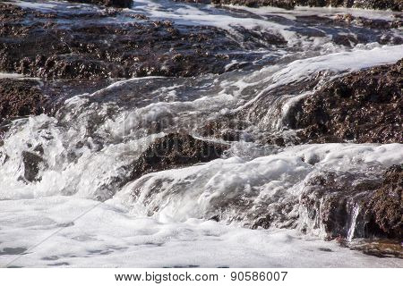 White Water Streaming Over Seaweed Covered Rocks