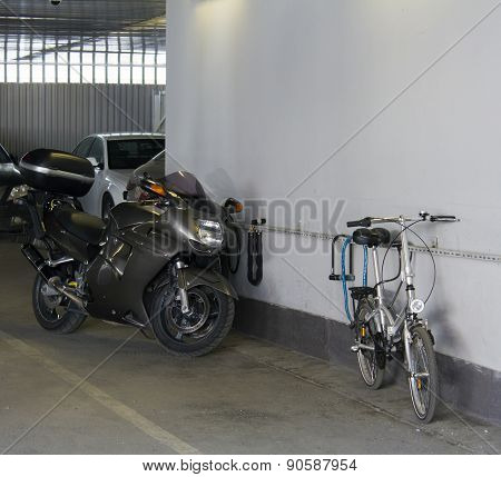 bicycle and motorcycle are on the guarded parking