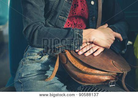 Woman Sitting On Train With Handbag
