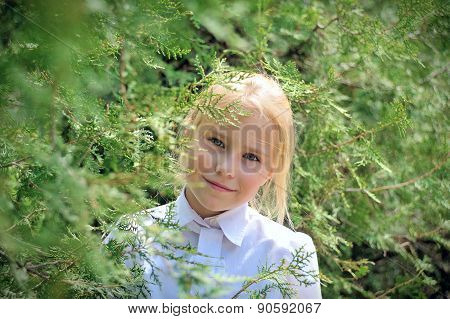The girl in a garden looks out because of foliage
