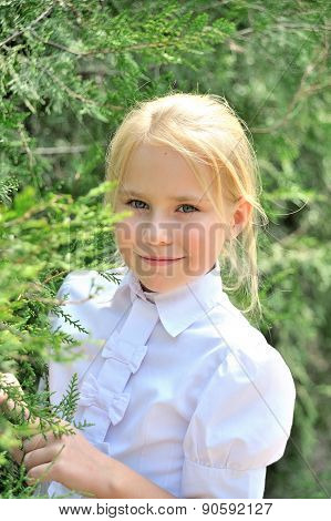 Portrait of the beautiful little girl in a park near thuyas